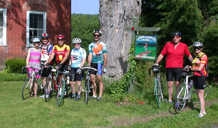Vermont cycling guests in front of biking sign